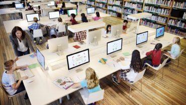 schüler im klassenraum vor bildschirmen