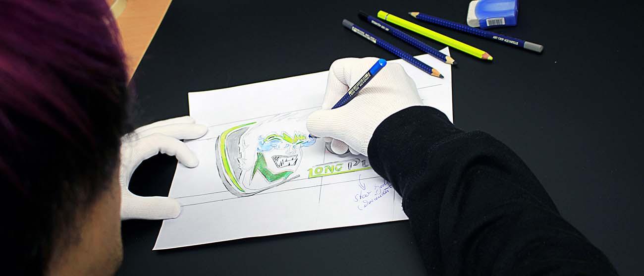 Hand mit Buntstift, wie sie ein Logo auf einem Blatt Papier zeichnet