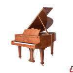 Ein Klavier aus rötlichem Holz auf komplett weißem Hintergrund