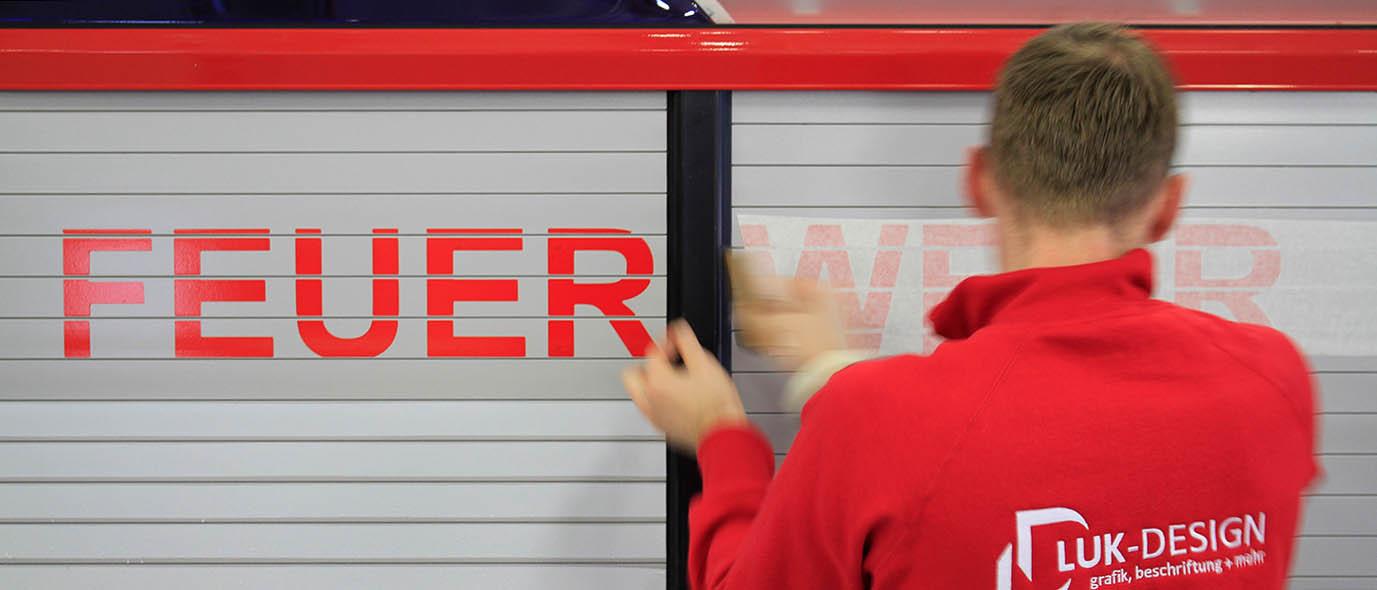 LUK-DESIGN Mitarbeiter beim Beschriften einer Feuerwehr