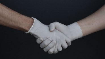 Hände in Gummihandschuhen reichen sich die Hand