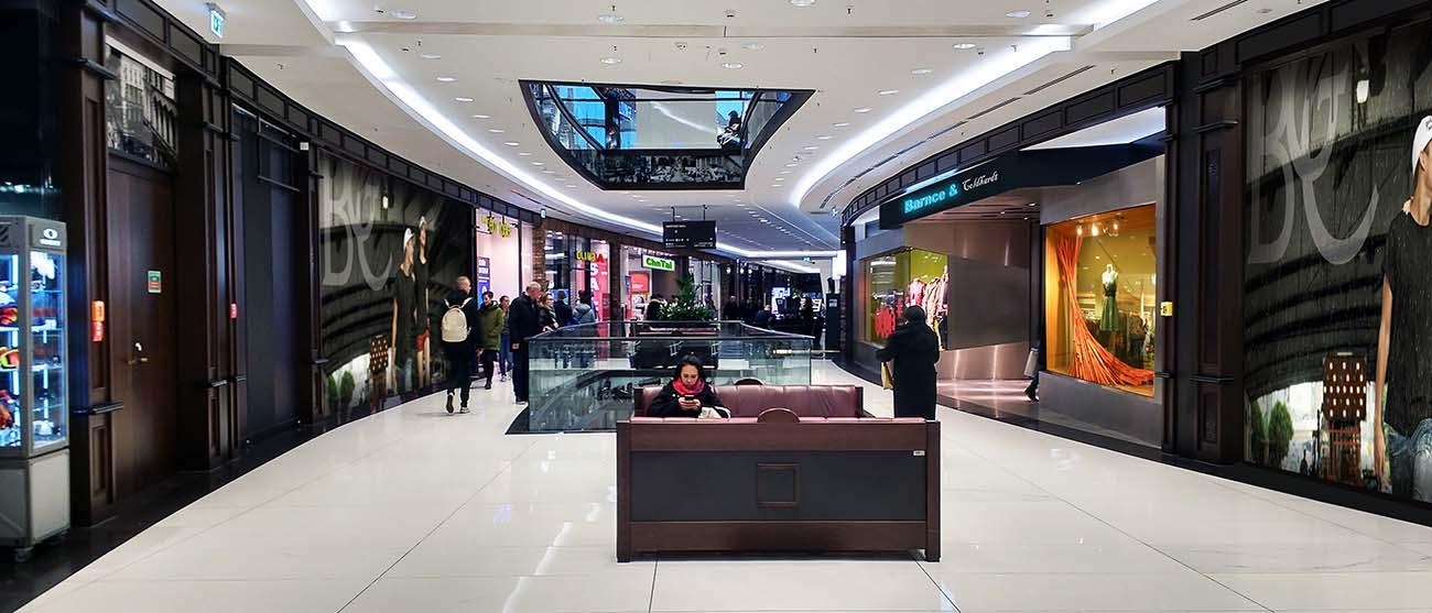 Blick auf eine Einkaufspassage mit großen Werbeflächen und Schaufenstern