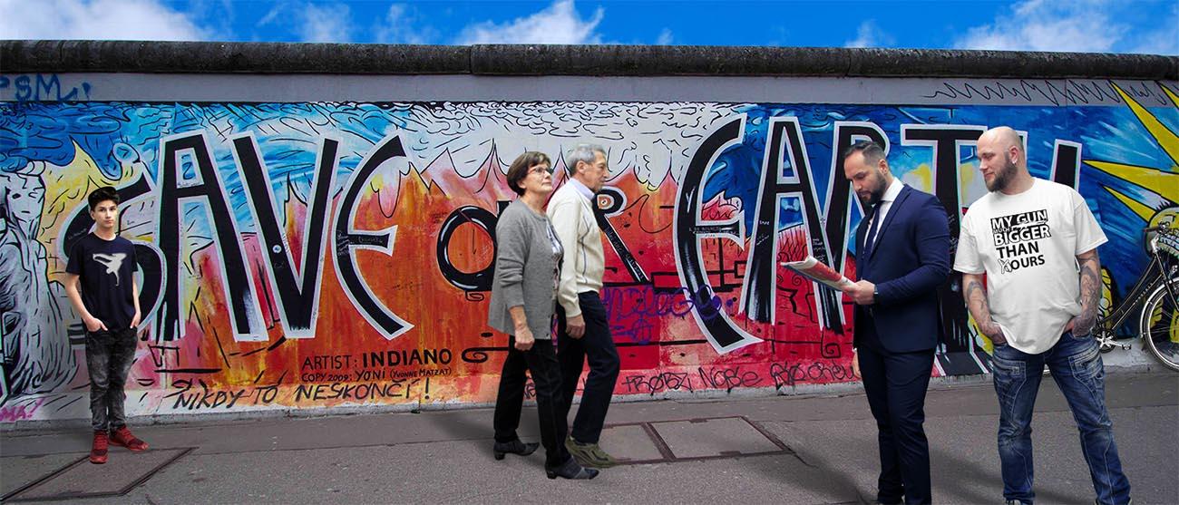 Menschen mit verschiedenen Textilien vor der Berliner Mauer